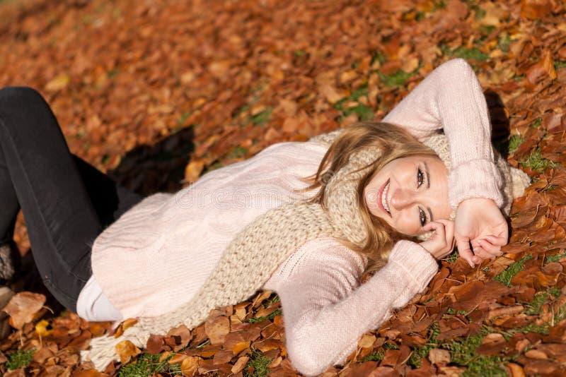 有帽子和围巾的年轻微笑的妇女室外在秋天 免版税库存照片