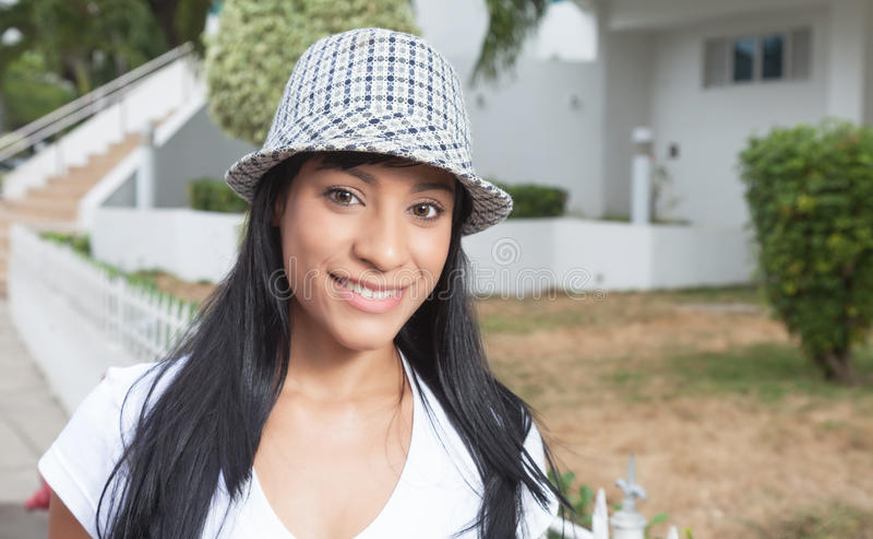 有帽子外部嘲笑的照相机的美丽的巴西妇女 库存照片