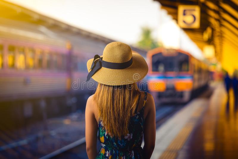 有帽子的妇女旅客在等待火车的铁轨附近 库存照片