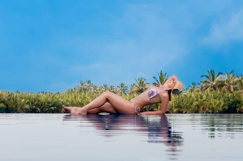 有帽子的妇女晒日光浴在游泳池边缘的 免版税库存图片