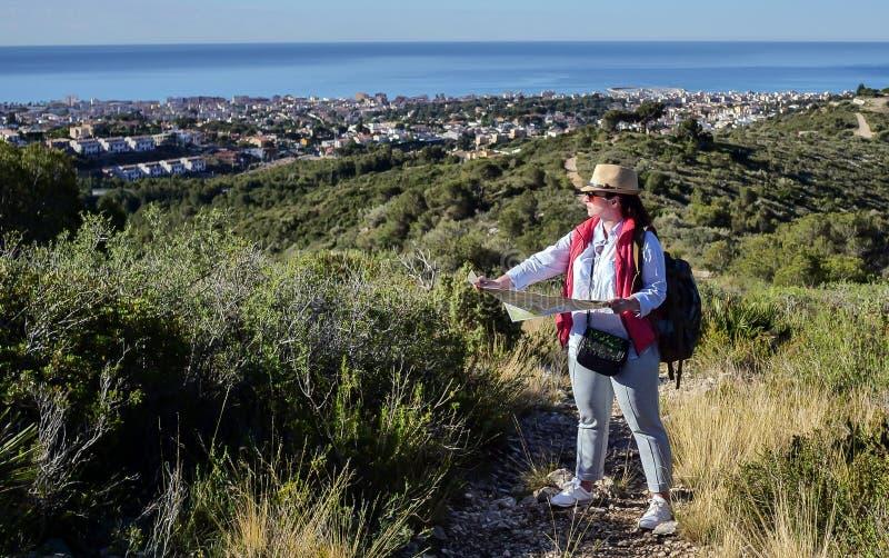 有帽子的年轻女人游人和区域看看的地图在小山下的城市 免版税库存图片