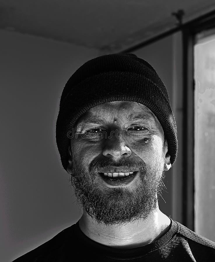 有帽子的微笑的人在黑白 图库摄影