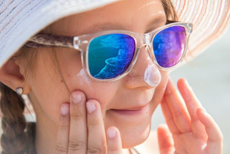 有帽子的微笑的女孩抹上在海滩的防护面霜 免版税库存图片