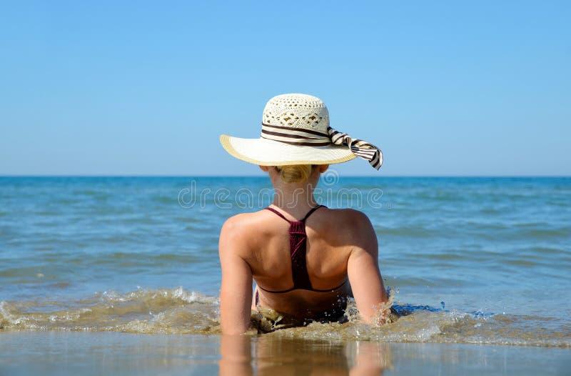 有帽子的白种人女孩在海滩 免版税图库摄影