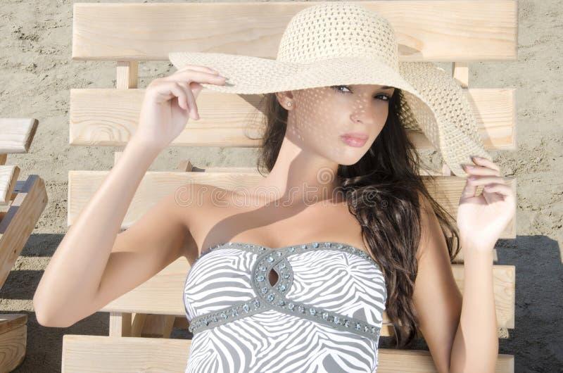 有帽子的美丽的女孩在海滩坐躺椅 免版税库存图片