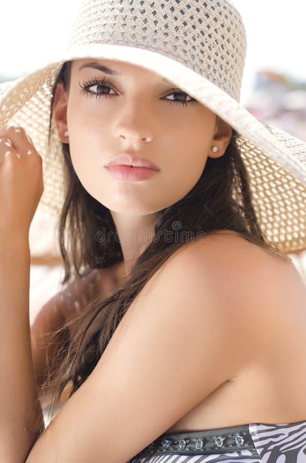 有帽子的美丽的女孩在海滩 免版税图库摄影