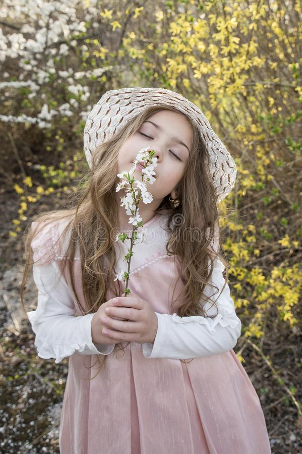 有帽子的美丽的女孩在自然气味花 免版税库存图片