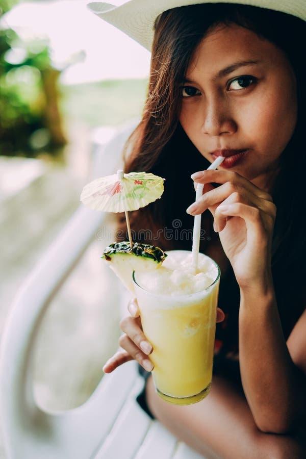 有帽子的美丽的女孩,喝新鲜和刷新的菠萝汁,暑假假期 库存图片