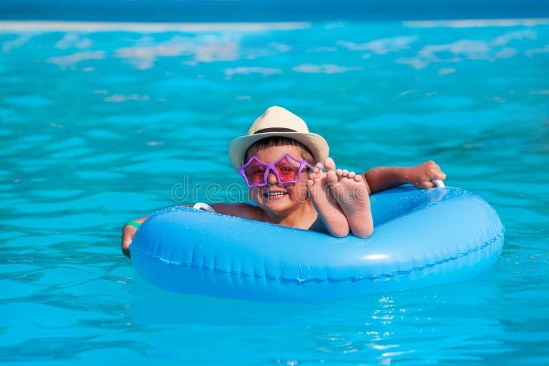 有帽子的,在可膨胀的圆环游泳的玻璃男孩 免版税图库摄影