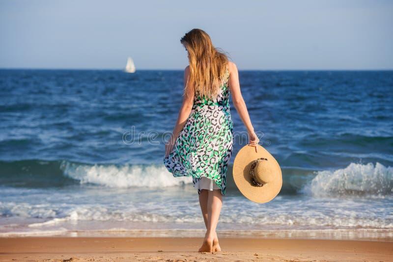 有帽子的年轻人赤足妇女走在海洋海滩的晴朗的热的天 免版税库存图片