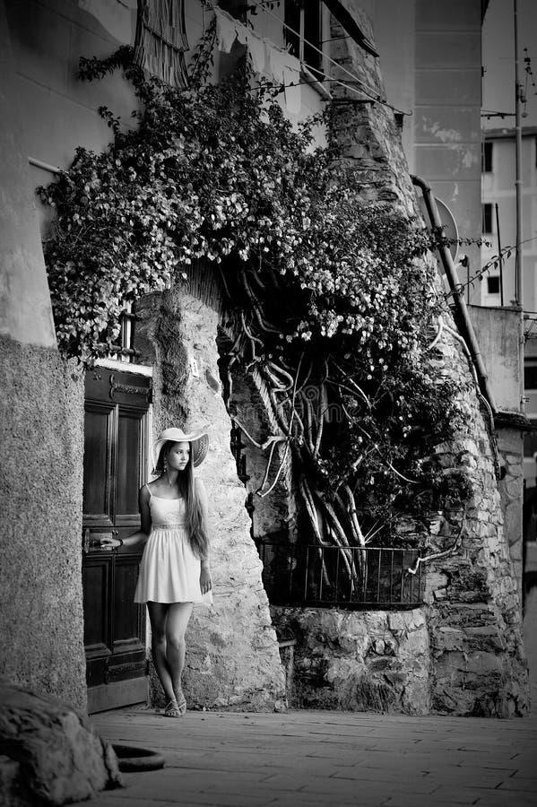有帽子的年轻美丽的女孩和夏天在葡萄酒门附近穿戴摆在 免版税图库摄影