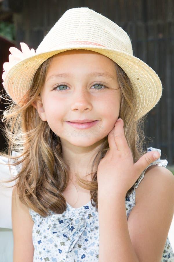 有帽子花的美丽的小女孩在户外她的头 免版税库存图片