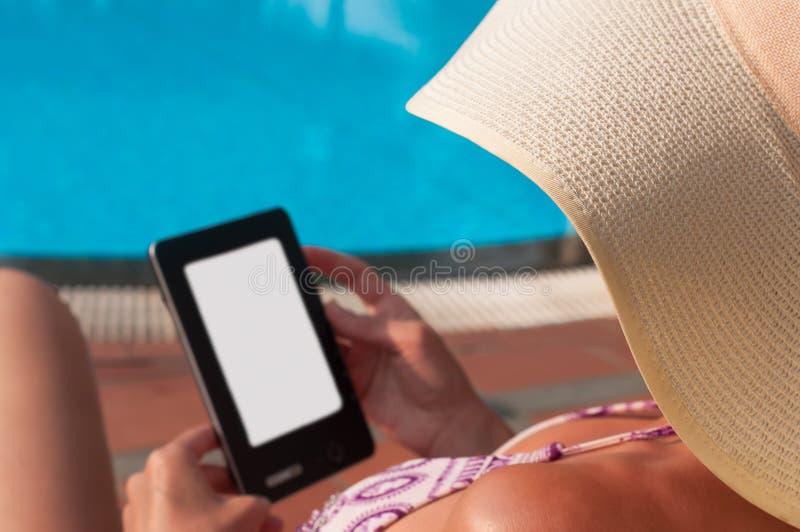 有帽子读书e书的妇女 免版税库存照片