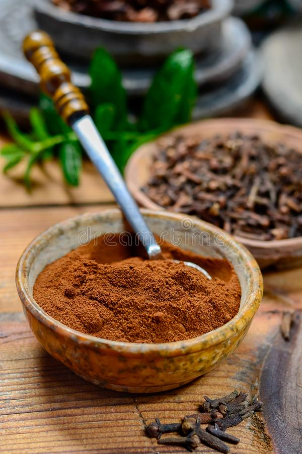 有干丁香芽和丁香粉末的碗,用于虚构和传统医学,关闭,香料汇集 库存图片