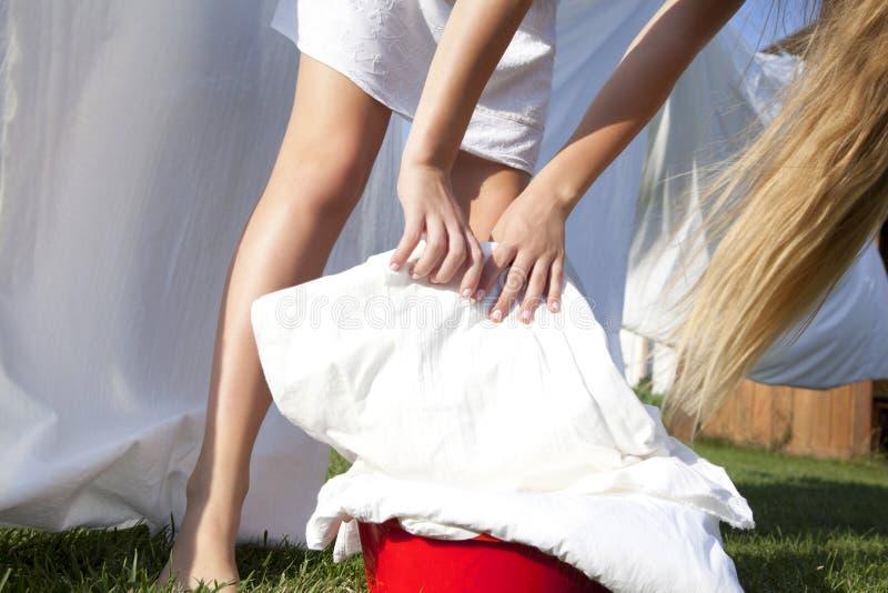 有干净的亚麻布水池的年轻女人挂上了在晒衣绳的板料 免版税图库摄影