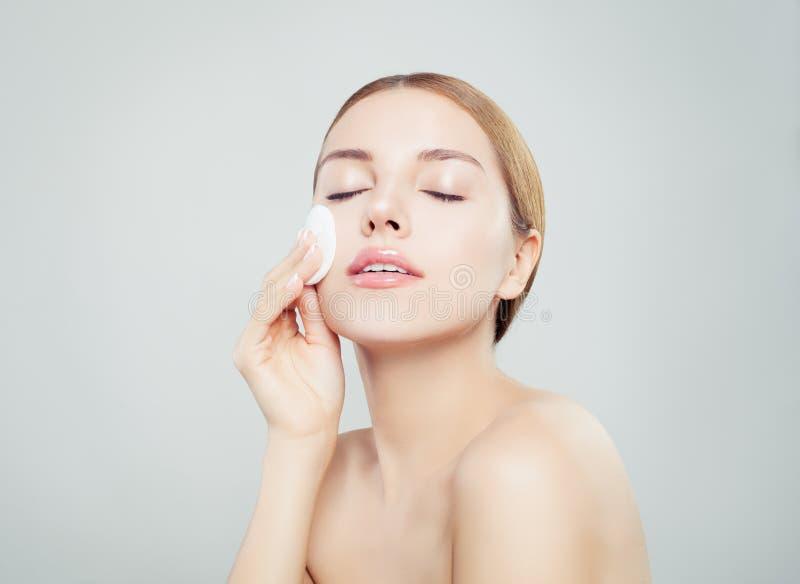 有干净的化装棉的美丽的年轻女人 面部治疗 库存图片