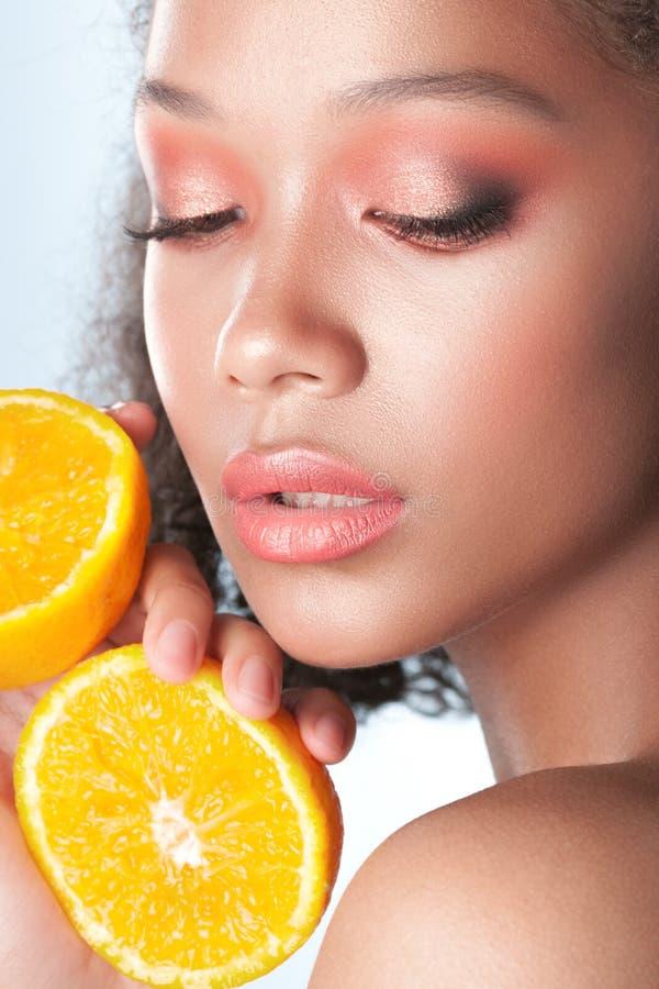 有干净的完善的皮肤的年轻美丽的黑人女孩与柠檬特写镜头 库存图片