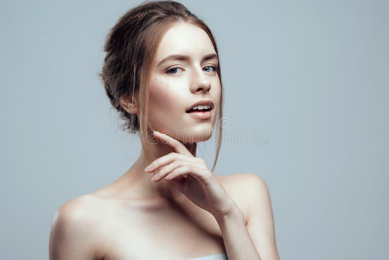 有干净的新鲜的皮肤的特写镜头美丽的少妇接触她的面孔 自然秀丽和温泉 图库摄影