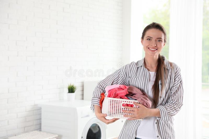 有干净的洗衣店篮子的年轻女人  免版税图库摄影