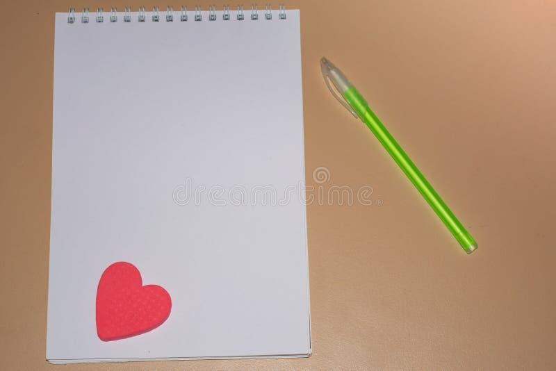 有干净的白皮书的笔记本在桌上的一支美丽的绿色笔旁边 图库摄影