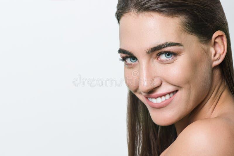 有干净的皮肤、自然构成、蓝眼睛、长期平直的健康头发和白色牙的微笑的妇女在白色背景 库存照片