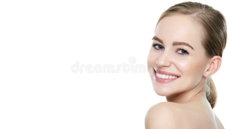 有干净的皮肤的美丽的年轻白肤金发的微笑的妇女,自然构成和完善白色牙 免版税库存图片