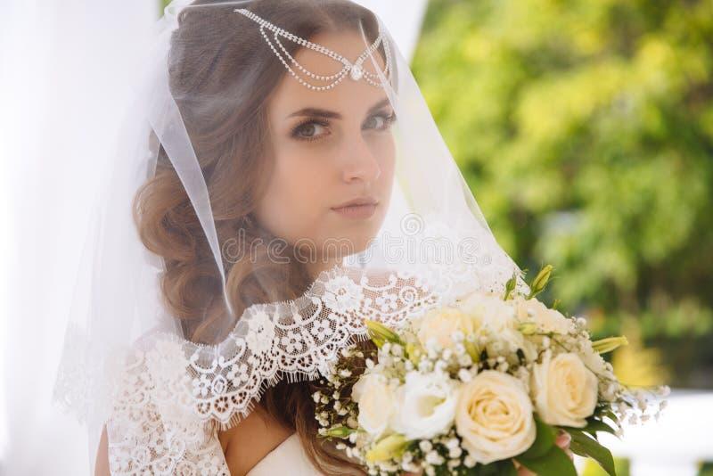 有干净的皮肤的,特写镜头美丽的年轻新娘 女孩` s面孔通过婚礼面纱 一个新娘的花束从白色的 免版税库存照片