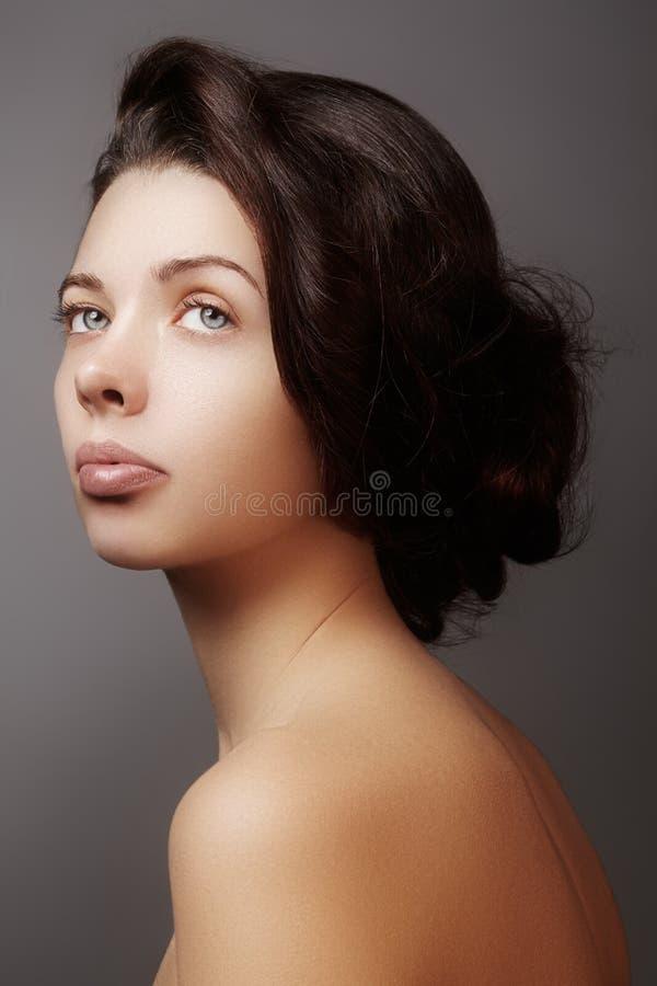 有干净的面孔的,发光的皮肤美丽的少妇,塑造自然构成,完美眼眉 逗人喜爱的小圆面包发型 温泉画象, 库存照片