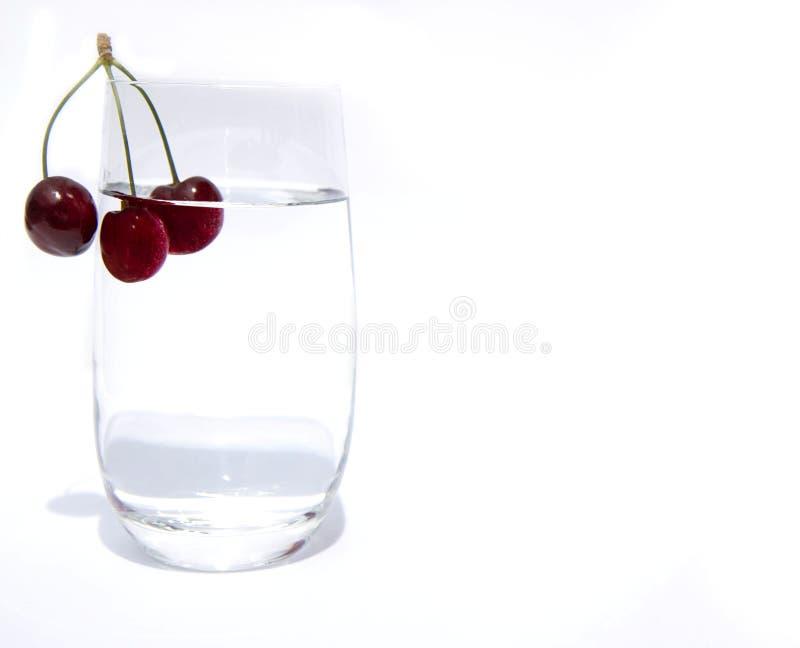 有干净的饮用水和三棵樱桃的一个玻璃杯子在边缘的一个分支 与水和樱桃的玻璃在白色 库存照片