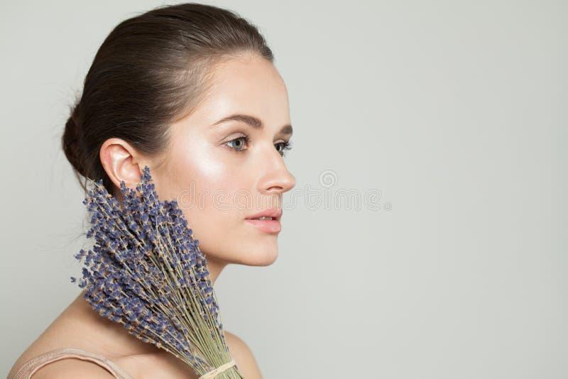 有干淡紫色花的美女 库存图片