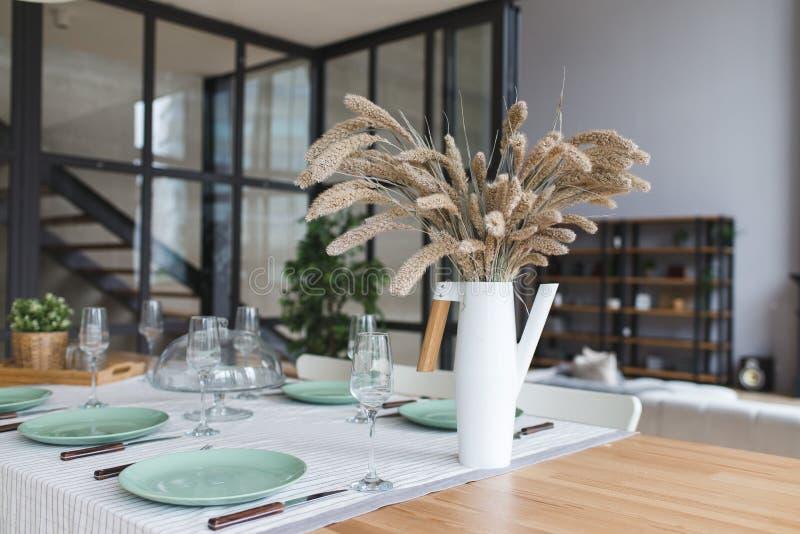 有干燥花的一个花瓶在桌上 有木和白色细节的,minimalistic内部斯堪的纳维亚经典厨房 舒适家 库存照片