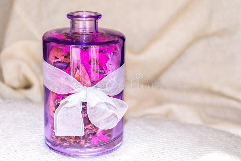 有干花和一把白色弓的玻璃花瓶 免版税库存图片