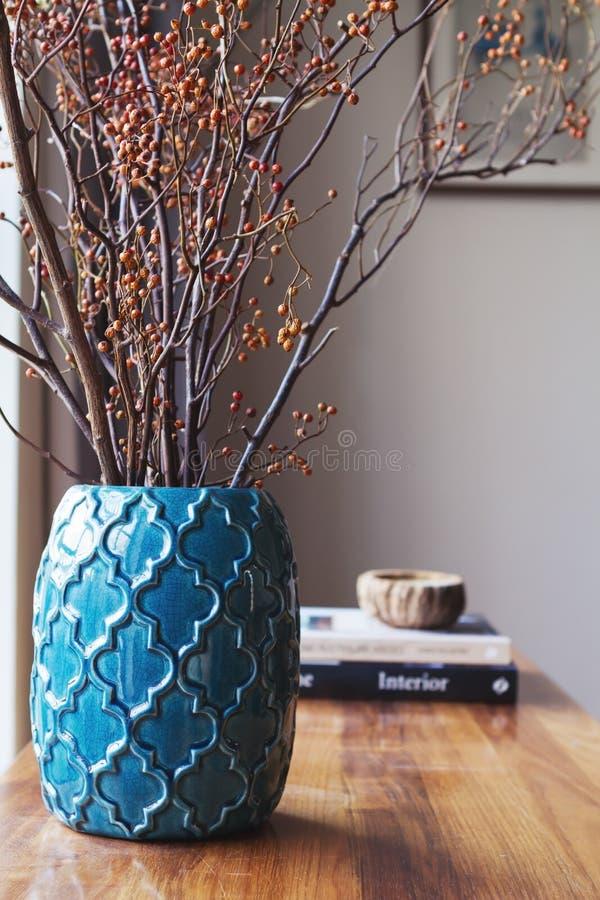 有干莓果棍子安排的小野鸭蓝色摩洛哥花瓶 库存图片