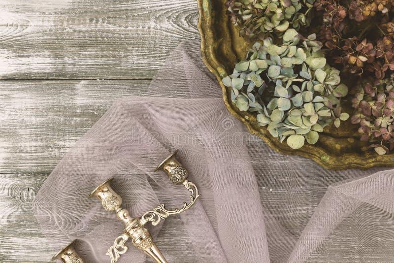 有干蓝色八仙花属花和一个银色烛台的葡萄酒盘子在一张灰色桌上 平的样式 复制文本的空间 免版税库存照片