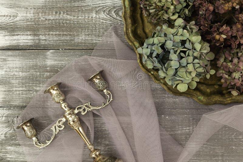 有干蓝色八仙花属花和一个银色烛台的葡萄酒盘子在一张灰色桌上 平的样式 复制文本的空间 库存图片