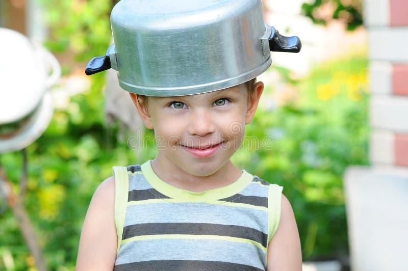 有平底深锅的一个孩子在他的头 有平底深锅的孩子 愉快的孩子沉溺 平底深锅帽子的一个孩子 库存图片