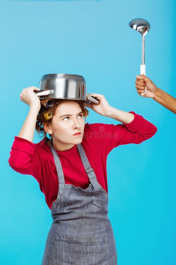 有平底深锅的好妇女在头从杓子掩藏 图库摄影