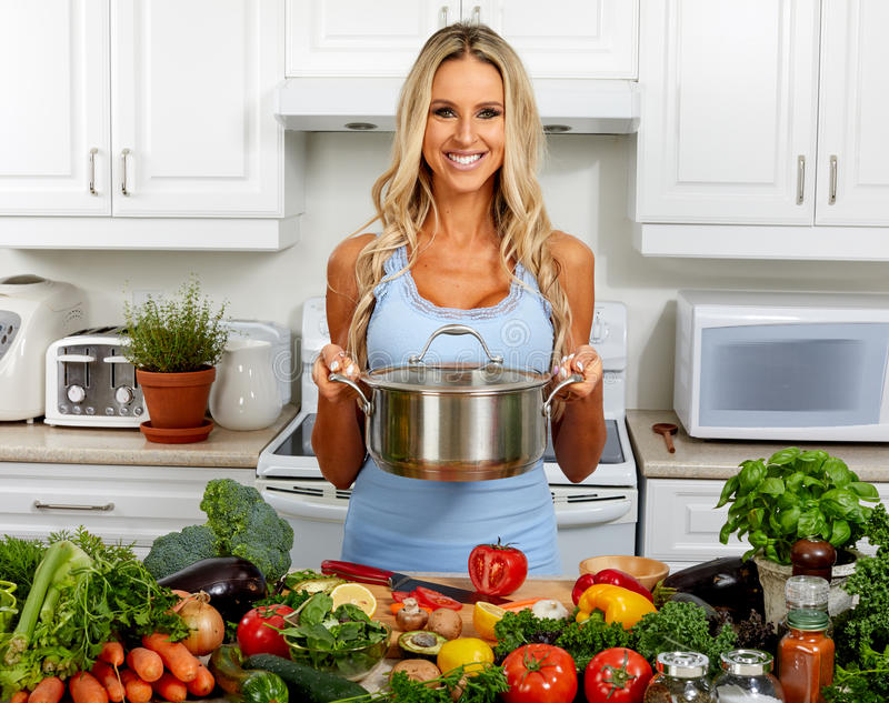 有平底深锅的少妇烹调在厨房里的 免版税库存图片