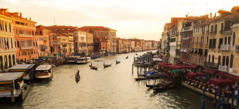 有平底船的船夫和乘客联盟的长平底船在从Ponte Rialto Rialto桥梁,日落的威尼斯,意大利的大运河视图 免版税库存照片