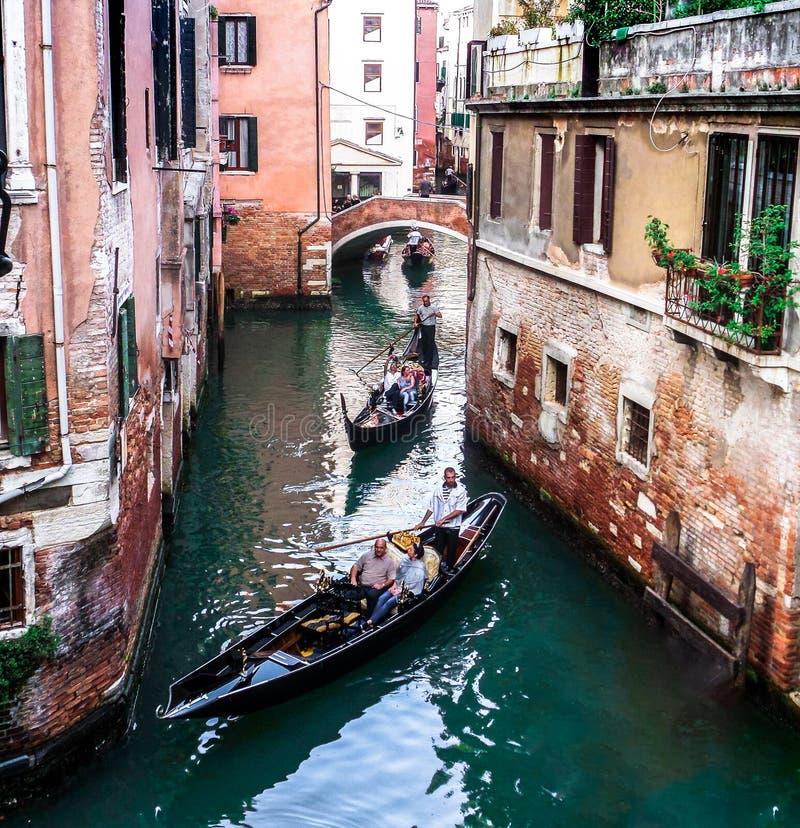 有平底船的船夫和五颜六色的大厦的威尼斯运河 免版税库存照片