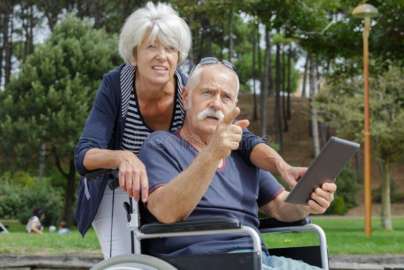 有平板电脑人的年长夫妇户外轮椅的 库存照片