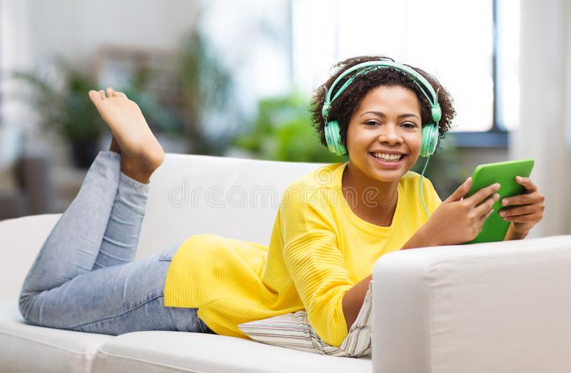 有平板电脑和耳机的愉快的非洲妇女 免版税库存照片