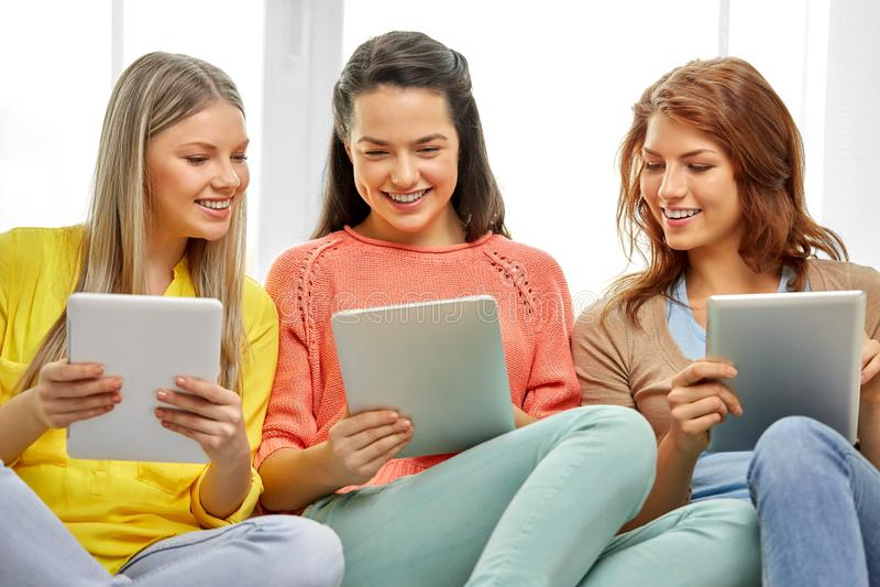 有平板电脑的三个微笑的十几岁的女孩在家 库存照片