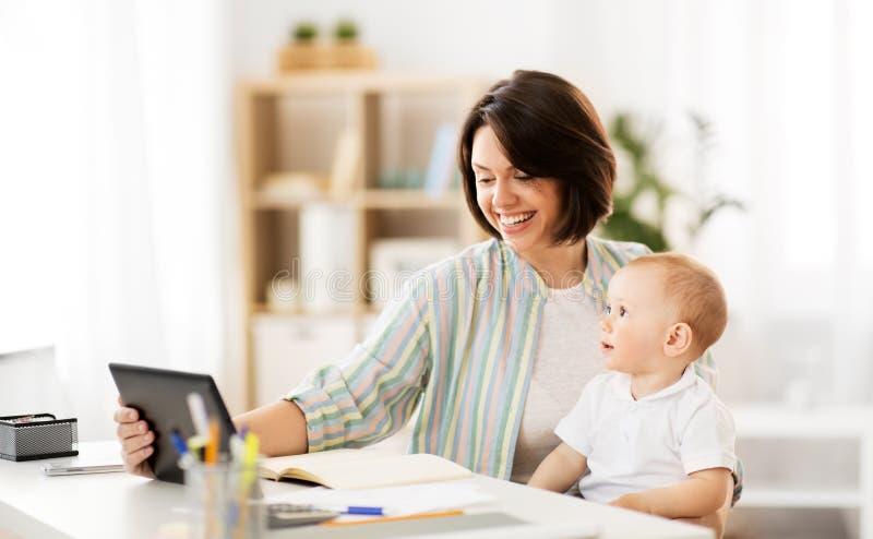 有平板电脑的工作母亲和婴孩在家 免版税库存图片