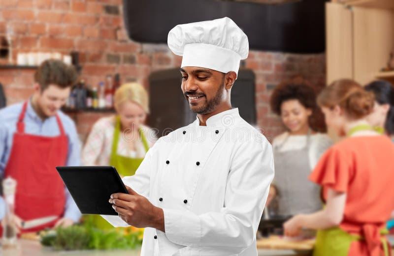 有平板电脑的男性印度厨师在烹饪课 免版税库存图片