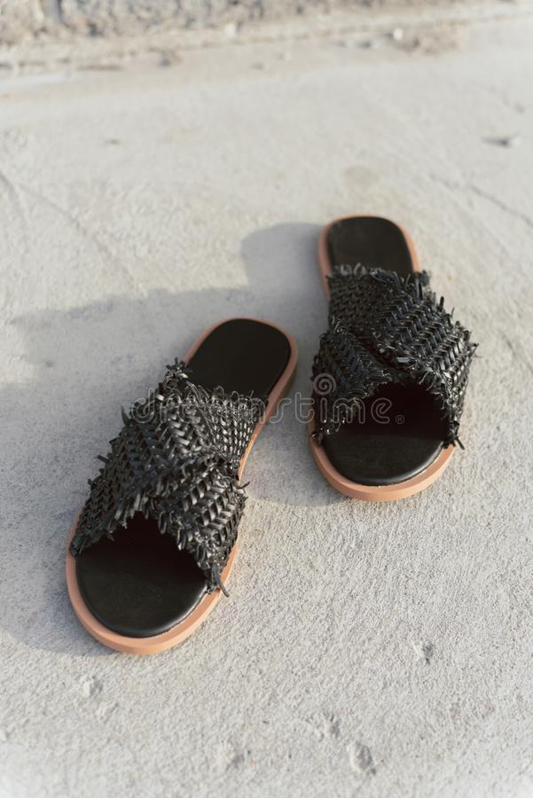 有平的脚底的黑柳条鞋子 没有腿的时髦的夏天板岩 在灰色沥青的时兴的女性拖鞋与阴影 库存图片