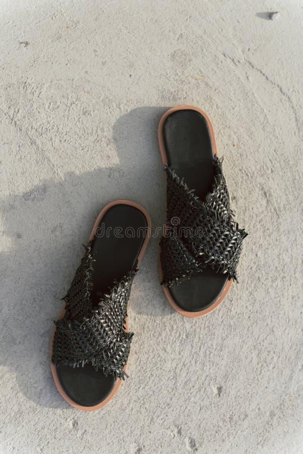 有平的脚底的黑柳条鞋子 没有腿的时髦的夏天板岩 在灰色沥青的时兴的女性拖鞋与 免版税库存图片