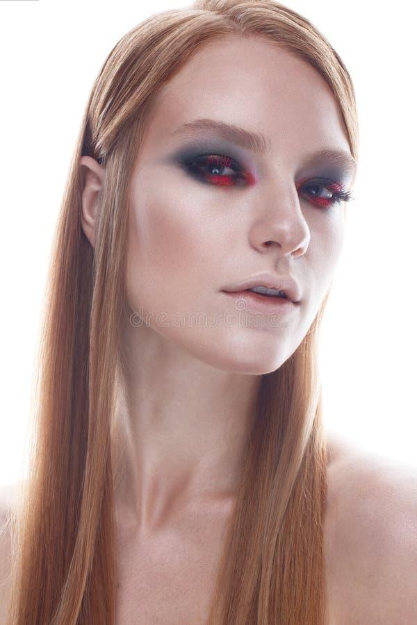 有平直的流动的头发和明亮的创造性的构成的一个女孩 与红色头发的美好的模型 面孔的秀丽 免版税库存图片