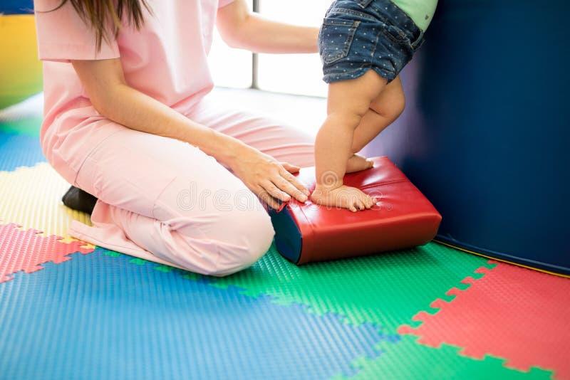 有平衡的治疗师帮助的婴孩 库存图片