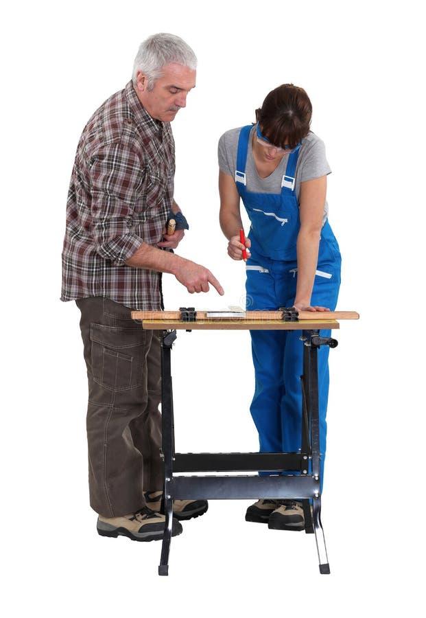 有年轻人实习生的木匠 免版税库存照片
